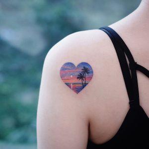 tatuaggio spalla cuore tramonto palme mare by @saegeemtattoo